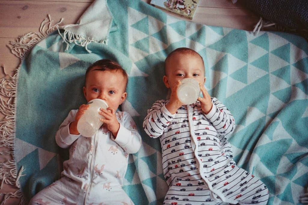two babies drinking from their bottles
